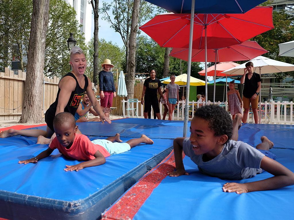Des enfants atterrissent sur des tapis en plein air
