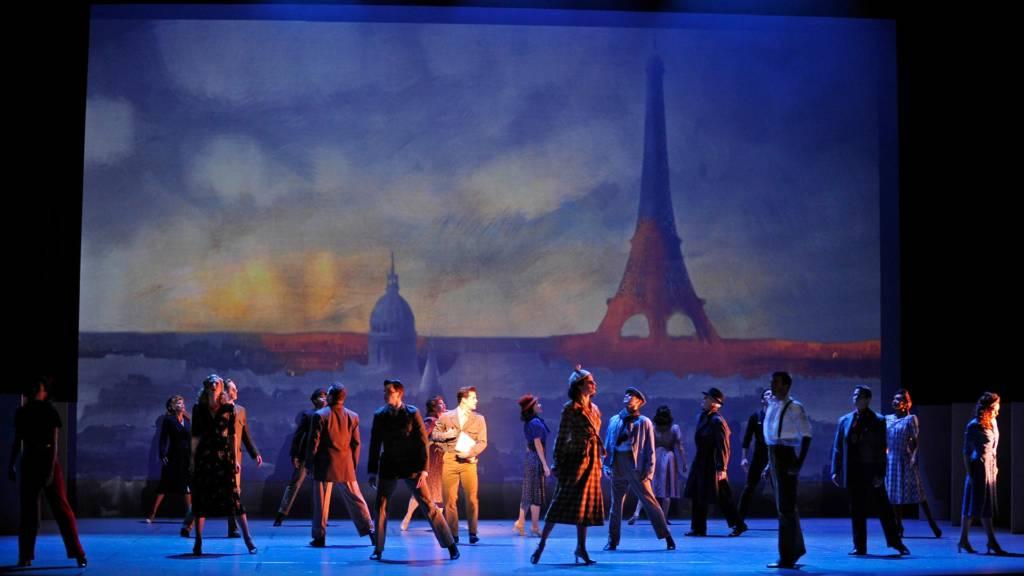 Groupe d'acteurs devant une peinture géante d'un lever de soleil sur Paris avec la tour Eiffel
