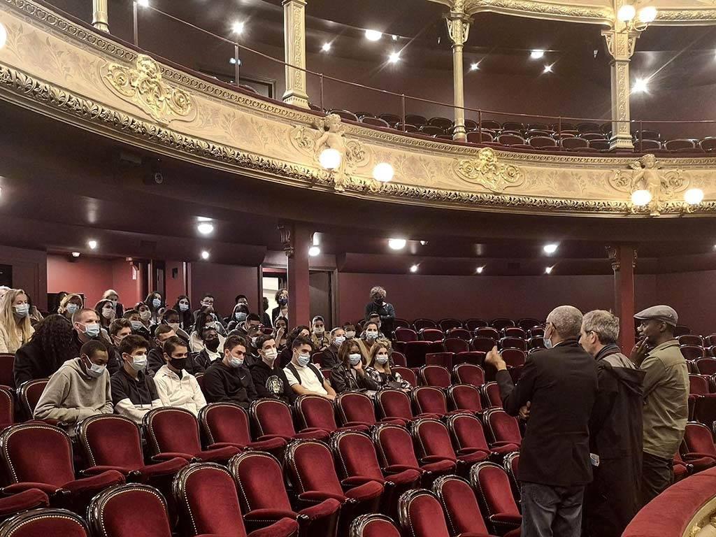 Des élèves discutent dans la grande salle avec le metteur en scène